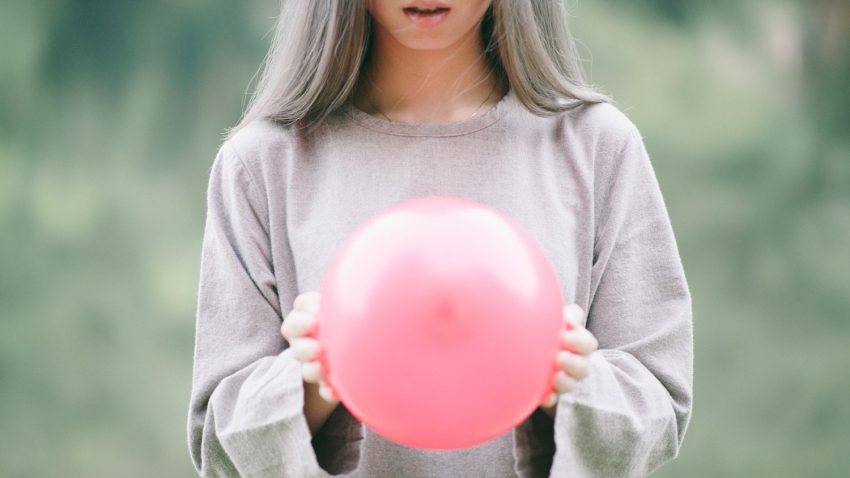 woman with pink ball balloon in hands