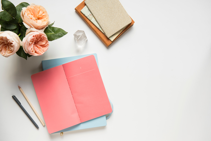 Rebranded my blog, flat lay of pink roses, two journals in pink and blue on desk