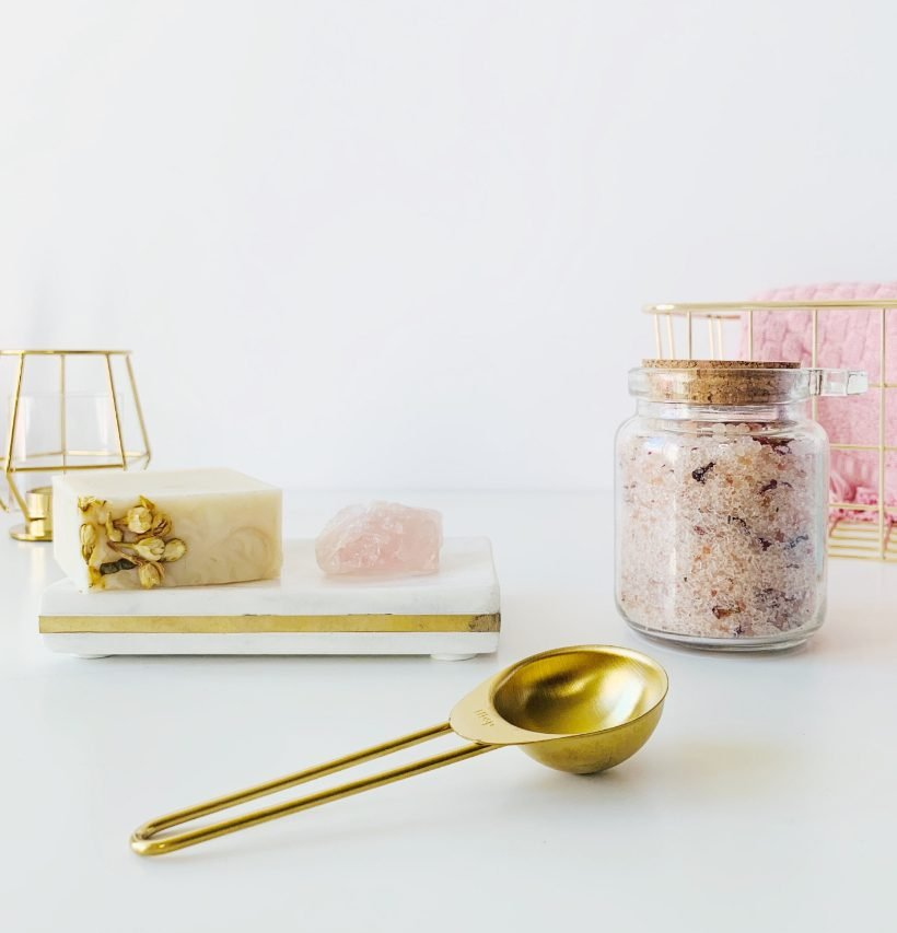 Home spa day, scrub in hermetic jar, next to golden spoon, purposeful habits